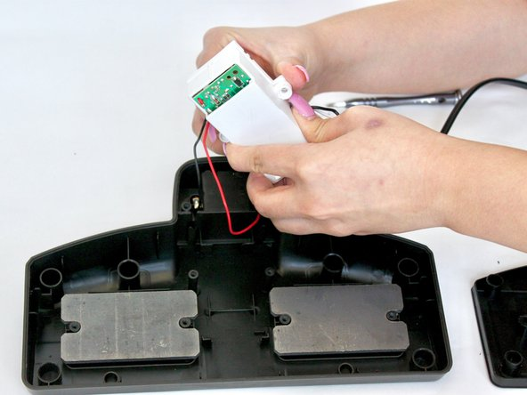 Using your hands, gently pull apart the two halves of the white battery cover to get to the battery