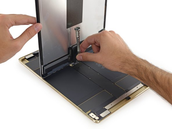 Image 1/3: This isn't quite [https://www.ifixit.com/Teardown/iPad+Air+2+Teardown/30592#s71618|what we're used to|new_window=true]! With the logic board situated in the ''center'' of the iPad, the display cables connect in the very middle of the device, so we can't even lay the display down while we work.
