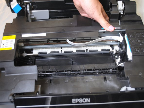 Take the right side of the bar of plastic that runs across the top of the inside of the printer and push it towards the left side of the printer.
