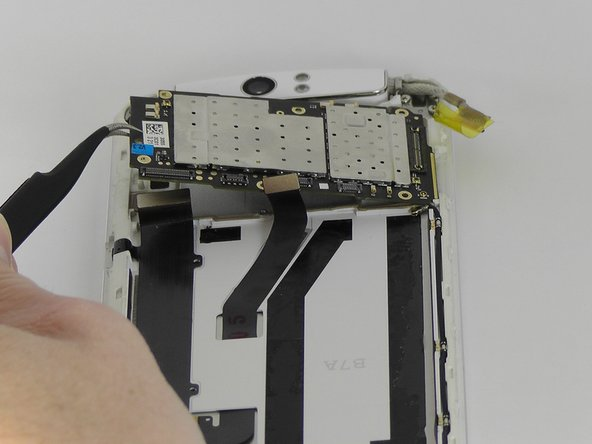 Use tweezers or your fingers to remove the motherboard.
