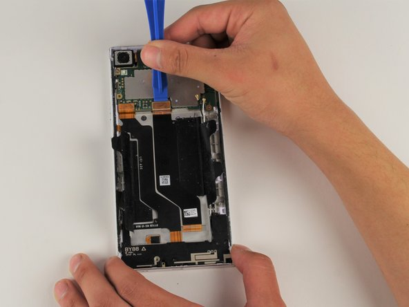 Use your iFixit Opening Tool to remove the power button flex (the left orange tab) from the motherboard.