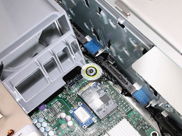 Image 2/2: Using a long-handled, magnetized #1 Phillips screwdriver, remove the screw at the top rear of the front fan assembly that mounts the assembly to the logic board.
