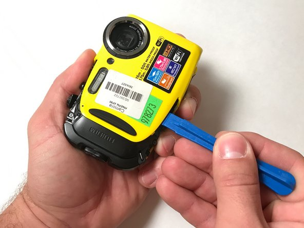 It is now safe to remove the yellow front panel. While using your plastic opening tool, gently pry the front panel away from the camera.