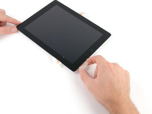 Löse den Kleber entlang der linken unteren Ecke mit dem Pick, dass sich noch an der Unterkante des iPads befindet.