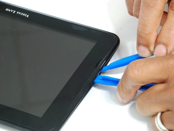 Using the large plastic opening tool, start along a side of the device and apply light pressure in the seam between the top and bottom outer covers.
