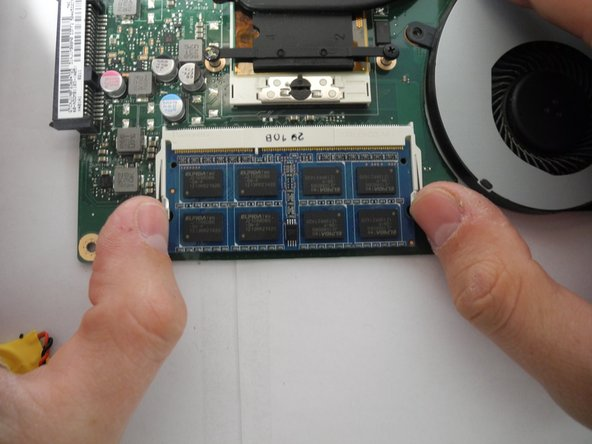Image 2/3: When reassembling, slide RAM in as far you can at a 45 degree angle and snap it down into place.