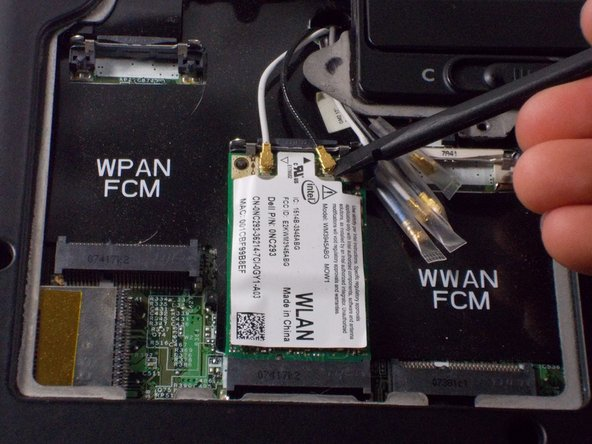 Use the spudger to lift the small wires connecting to the Wi-Fi card.