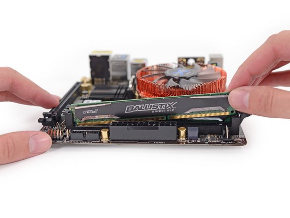 Image 2/3: A nook in the motherboard cowling gives you access to the RAM before you get this deep. But they won't be easy to finagle out of their slots, even with only one clip apiece to secure them.
