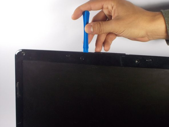 Using a plastic opening tool carefully pry along the edges of the screen bezel to remove it.
