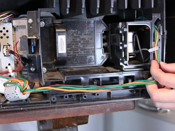 Pull up and unsecure the orange and green power connection wires that are being held down by the white clamps and black cable hooks.