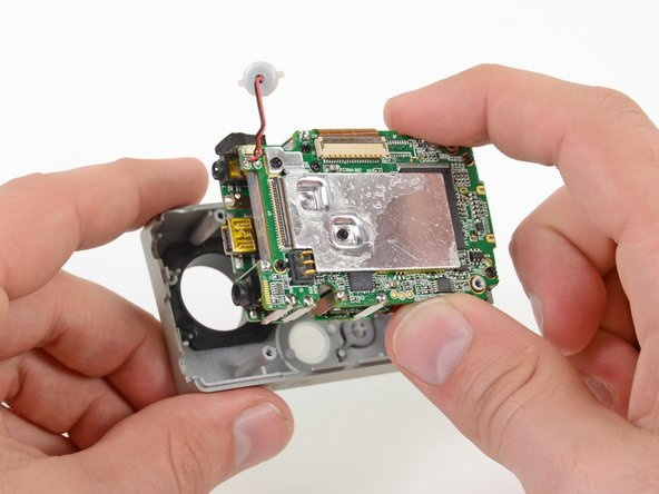 Gently grab the edges of the motherboard assembly and lift it out of the front case.