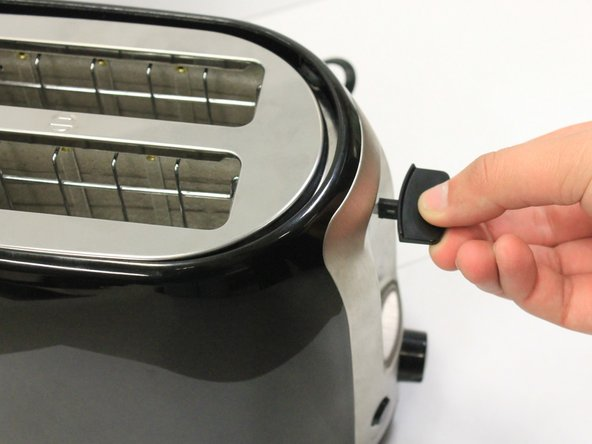 Pull lever tab away from the toaster with force (after pushing in the small tab located to the left)
