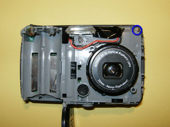 Remove the one screw on the top left of the camera. It this holds the back case on to the midframe.
