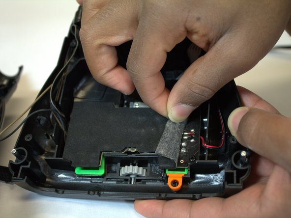 Now that your device is open, remove the Styrofoam pad that covers the main circuit board. The adhesive should allow you to remove and replace it with ease.