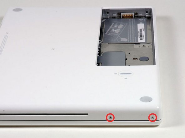 Remove the two Phillips screws from the optical drive side of the computer.