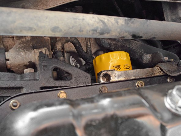 Image 1/3: Reposition the oil drain pan so that it catches the oil that will spill when you remove the oil filter.