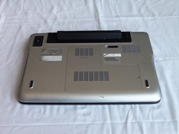Flip over the laptop with the bottom battery compartment facing up.