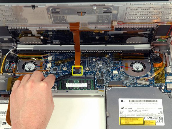 Image 1/1: Disconnect the trackpad and keyboard ribbon cable from the logic board, removing tape as necessary.