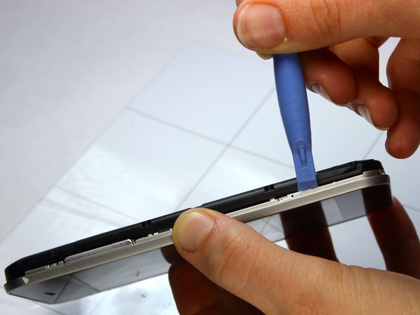 Gently run a plastic opening tool down along the left and right sides of the phone to separate the black midframe assembly from the silver display casing.