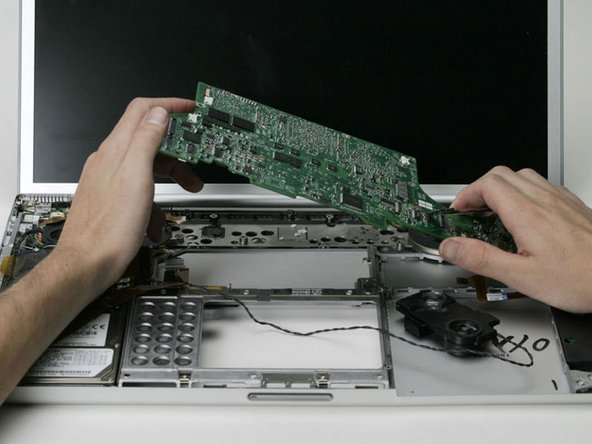 Image 1/1: Once the logic board clears the ports, slide it out to the left.
