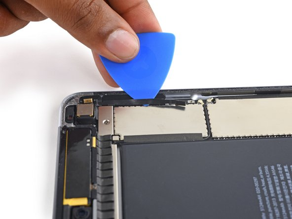 Slide an opening pick underneath the volume control buttons' ribbon cable to peel it away from the adhesive below.