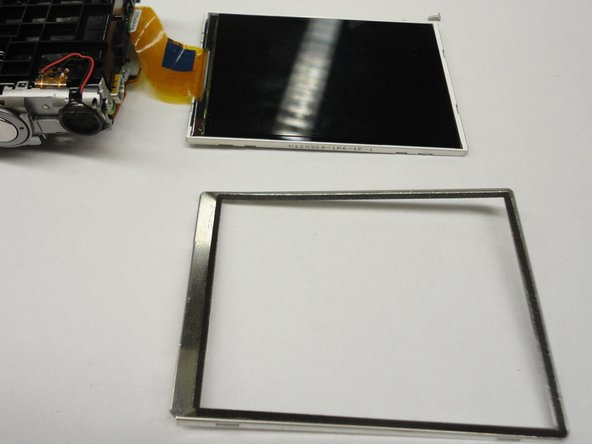 The metal frame of the screen can be removed using a thin spatula or spudger. After the frame is removed the part of the ribbon connected to the screen is accessible.