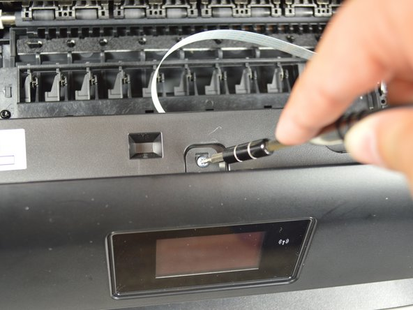 Using the hex screwdriver, remove the 2.0 mm x 14 mm screw that binds the front cover to the printer body by turning the screw counterclockwise.