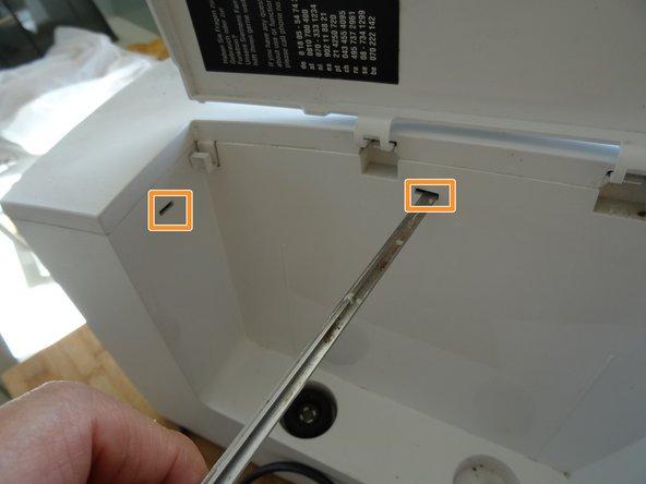 Drücke mit einem Flachschraubendreher in die Öffnungen auf der Seite mit dem Wassertank. Dadurch werden die Rasten der Oberseite gelöst.