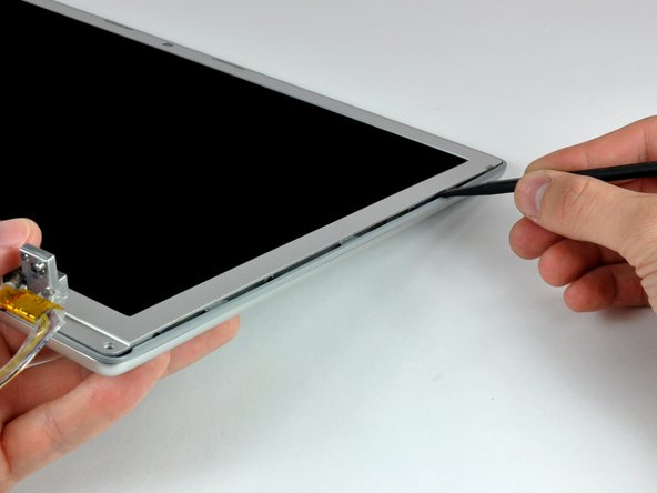 Image 3/3: With the spudger still inserted, rotate it away from the display to separate the front and rear bezels.