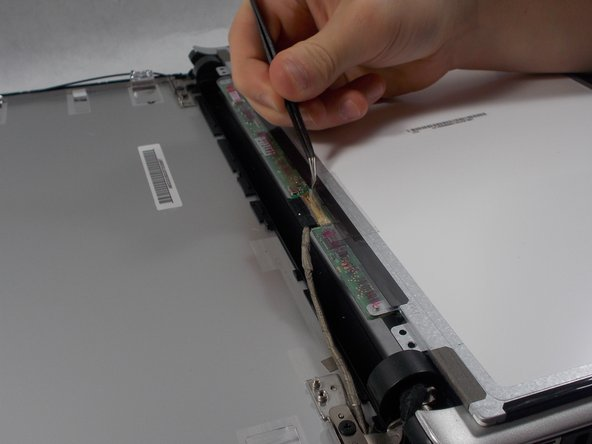 Use the tweezers to peal back the tape over the wire connector on the bottom of the screen