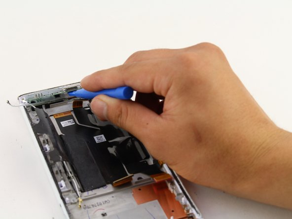 Pull up with your iFixit Opening Tool to remove the charging port PCB board.