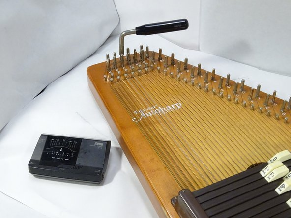 The string should be taut. Now you are ready to tune the autoharp. Use the electronic tuner and adjust tension to the correct pitch. Adjust pitch by turning the tuning hammer in small increments. Turn  counter clockwise (left) to lower the pitch and clockwise (right) to raise pitch.