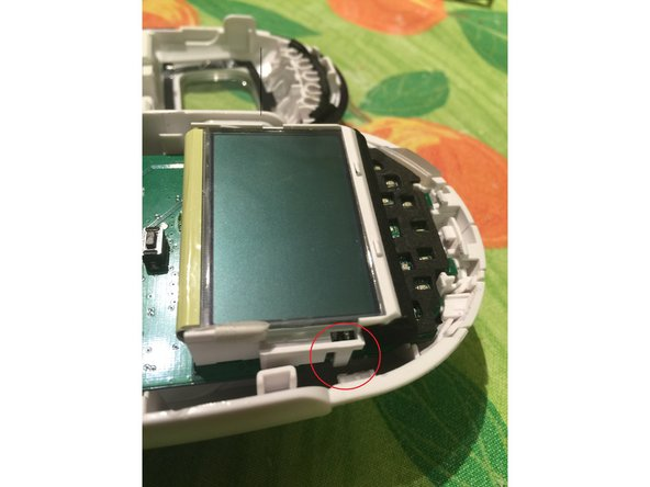 The LCD is held on by a pair of small plastic lugs, one each side.  Release these one at a time, while gently lifting the LCD up from the board.