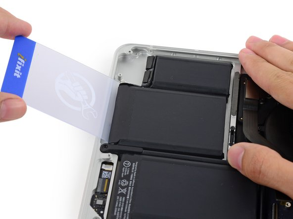 Image 1/3: Insert the plastic card between the second left-most battery cell and the upper case to cut the adhesive joining the two, and pry the cell up from the case.