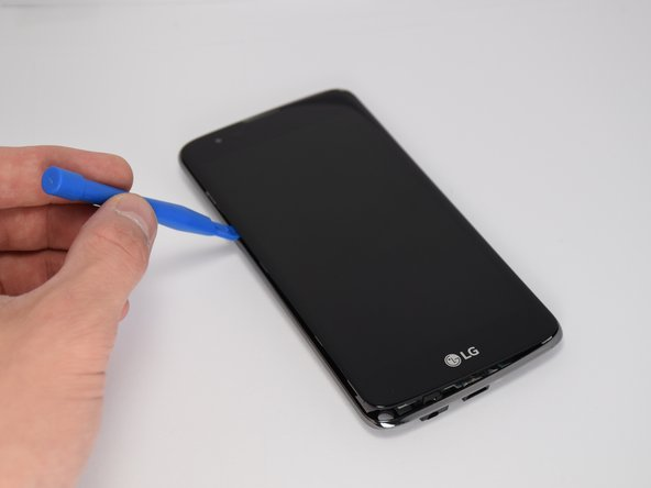 Use a plastic opening tool to separate the screen from the outer frame.