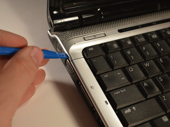 Use the plastic opening tool to get underneath the plastic bar above the keyboard, pry upwards. Pry the keyboard upwards gently.