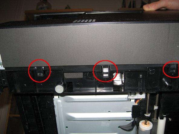 Linkes Gehäuseteil durch vorsichtiges Lösen der 3 Klammern am Boden entfernen.
