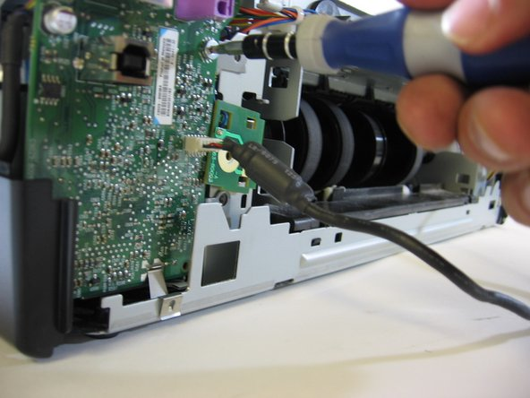 Now, move on to the screws attached to the motherboard (that collection of metal and plastic stuff attached to a green piece of plastic). Remove each of the screws, set aside, and remove the motherboard from it's base. DO NOT attempt to pull it completely out - there are important wires still attached to it.