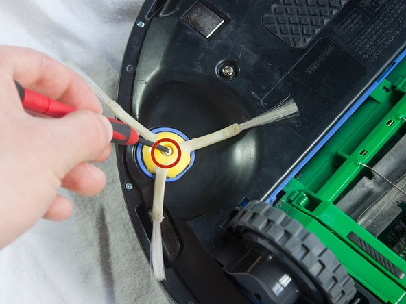 While holding the side brush in place, use a Phillips #1 screwdriver to remove the 4.5mm screw from the center of the brush.