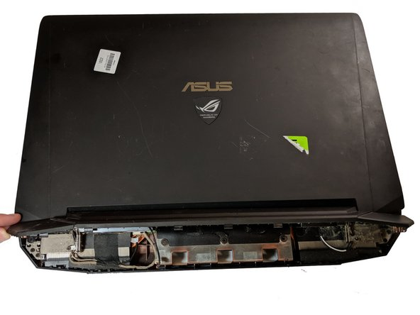 Take a metal separater and gently pry open the back end of the laptop halves.