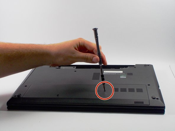 Remove the bottom cover by removing the 4 mm screw using a PH-0 Phillips screwdriver that secures the base cover to the laptop base.