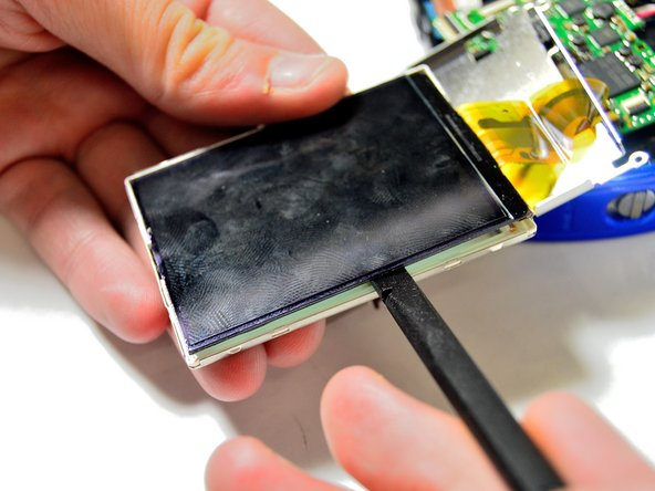 Take the spudger and wedge it very carefully between the LCD screen and the very thin and fragile frame.