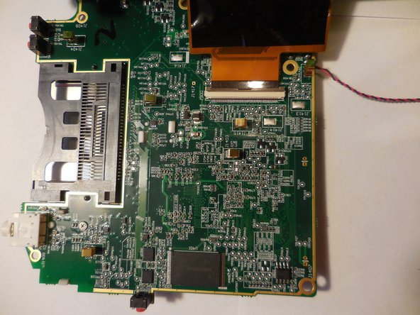 Lift the motherboard up exposing the fourth and final wire. Once you life up the motherboard you will need to pull down on the wire to disconnect.