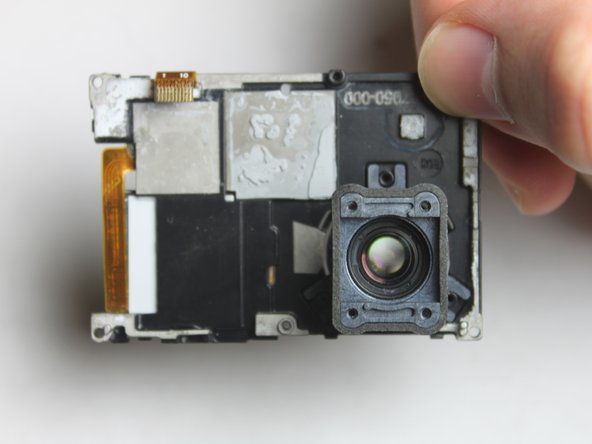 Once the ribbon cable is disconnected, you can remove the black plastic bracket which holds the camera lens.