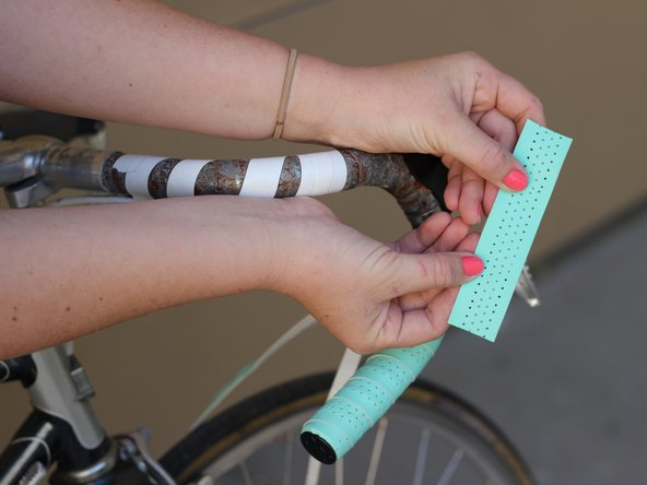 Take the extra piece of bar tape provided and cut it to fit the back of the brake lever.