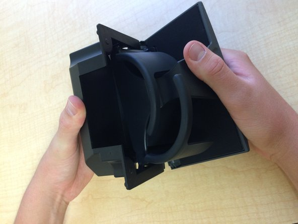 Reinsert the front part of the cup holder into the back part of the cup holder by reversing the steps you took to separate the front and back parts of the cup holder.