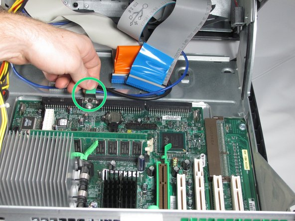 Pull the green tab toward the front of the PC to release the motherboard.