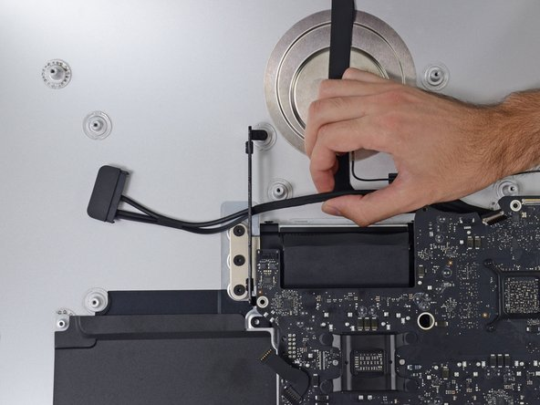 Image 1/3: Pull the cable and connector through the right hard drive bracket. Move the cable to the right side of the iMac, out of the way of the exhaust port.