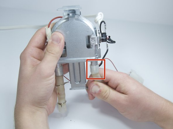 Remove the two rubber water tubes from the heating element by firmly pulling each at a 90 degree angle from the socket.