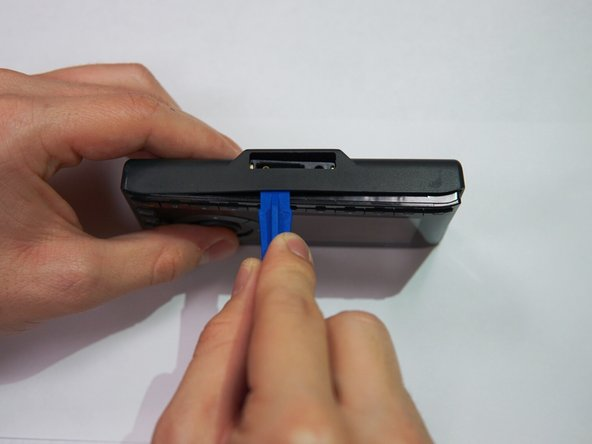 Apply pressure to the iFixit opening tool, pushing down until the the plastic casing pops off.